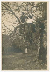 Ruth Patrick and Alice Mason in a tree below the bluff. Monument to the school house built under the direction of Captain Nelson Miner by the first Dakota Cavalry in 1864 appears in the background.